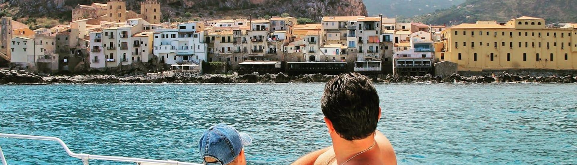 Participants on a boat trip to Cefalù with Sea Land Tours Cefalù look out over the coast of the Sicilian town.