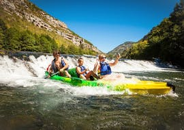 A family is having fun crossing one of the rapids of the Tarn during their 10km Canoe Tour in Gorges du Tarn with Le Soulio.