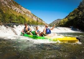 Une famille s'amuse en franchissant l'un des rapides du Tarn pendant leur sortie avec Location de canoë dans les Gorges du Tarn - 10 km avec Le Soulio.