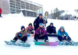 Children sit in the snow with their snowboards during their private snowboarding lessons for children & adults with the ski school Zell am See Outdo .