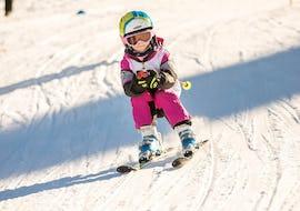 Kind fährt sportlich und mit gebeugten Knien die Piste hinunter während dem Kinder Skikurs (4-12 Jahre) - Alle Levels mit der Skischule Thomas Spenzel.