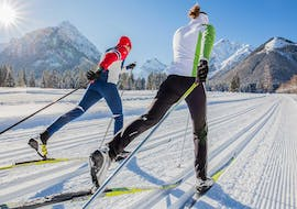 A man and a woman are gliding along the cross country track during their private cross country skiing lessons with ACT Sports Skischule.