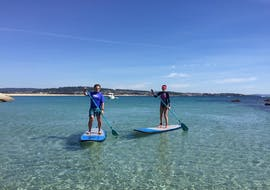 Two people do a stand up paddleboarding tour in the Rias Bajas with Waipia Surf School.