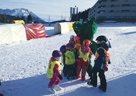 The children stand together with the ski school mascots on the playground and pose for the photo during the kids ski lessons with kindergarten (3-5 years) from the ski school S4 Snowsports Fieberbrunn.