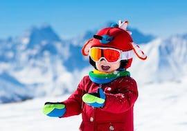 Ein Kind lächelt glücklich in die Kamera in der Berglandschaft während dem Snowboardkurs für Kinder (ab 7 Jahren) - Anfänger der Skischule S4 Snowsports Fieberbrunn.