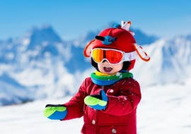 A child smiles happily into the camera in the mountain landscape during the snowboarding lessons for kids (from 7 years) - beginner of the ski school S4 Snowsports Fieberbrunn.
