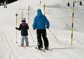 Skilehrer fährt mit seinem Schüler über die Übungspiste im Rahmen des Angebots Privater Kinder Skikurs - Alle Levels mit der Skischule Freedom Snowsports.