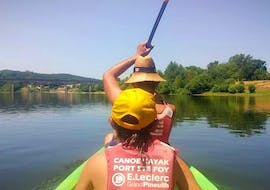 A parent and their child are paddling on the river during their 4km Canoe Rental on the Dordogne for Families with Canoe Kayak Port-Sainte-Foy.