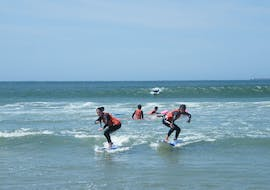 Two girls are learning how to surf during surfing lessons on Matosinhos Beach under the supervision of a certified surf instructor from Surfaventura.