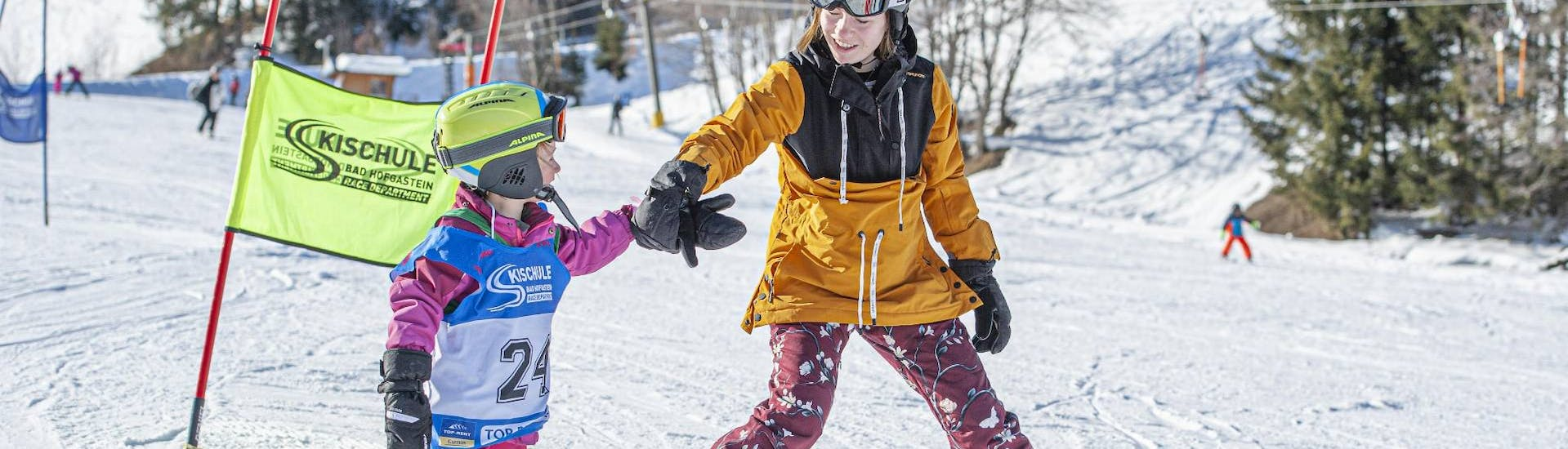 an older child is helping a younger one during their skids ski lesson for beginner at skischule badhofstein.