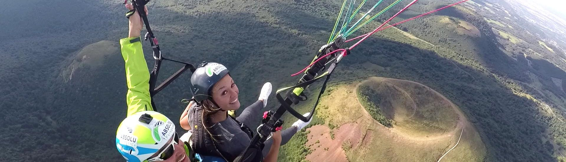 A paragliding enthusiast is happy to do a tandem paragliding flight with an experienced pilot from Absolu Parapente above the Puy de Dôme and the volcanoes of the Chaîne des Puys.