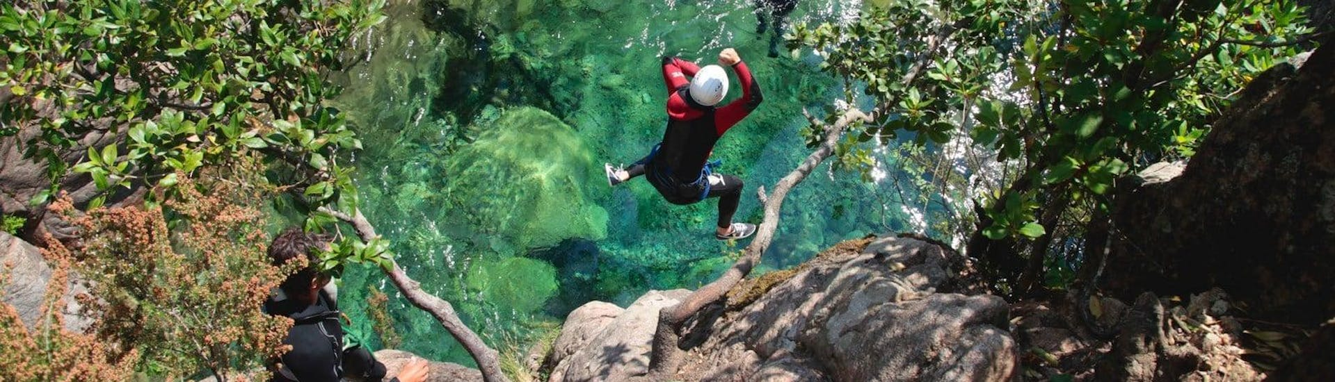 A canyoning enthusiast is jumping into an emerald green natural pool under the supervision of a qualified canyoning guide from Acqua et Natura which offers canyoning trips in Corsica.