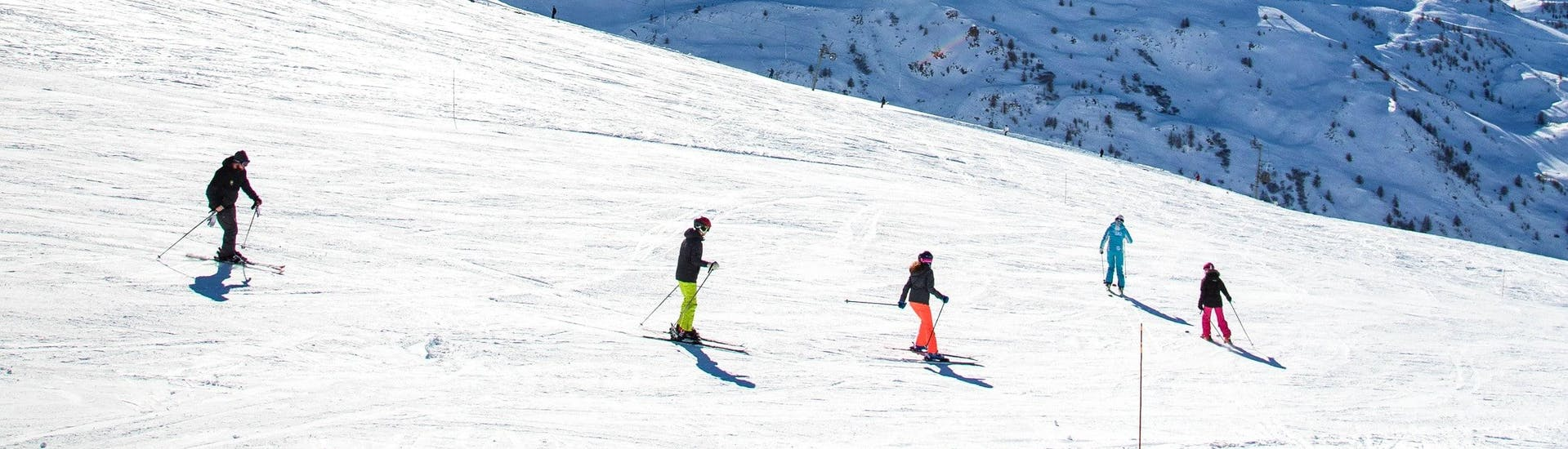 Skiers are skiing down a slope in confidence during their Adult Ski Lessons for All Levels with the ski school ESI Ski Family in Val Thorens.