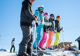 Skiers are standing at the top of a slope ready to start their Adult Ski Lessons for All Levels with the ski school ESI Ski Family in Val Thorens.
