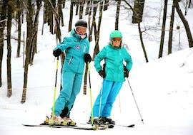 Los participantes levantan sus bastones de esquí al aire durante las clases de adultos para todos los niveles de Ski Life Escuela de Esquí Baqueira.