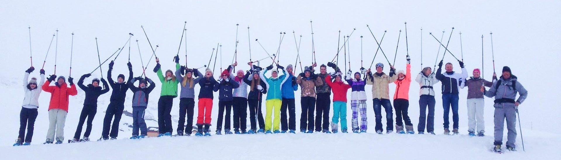 Skiers are standing next to each other at the top of a slope with their ski poles in the air, waiting to start their Adult Ski Lessons (from 14 y.) for All Levels with the ski school Evolution 2 Val Thorens.