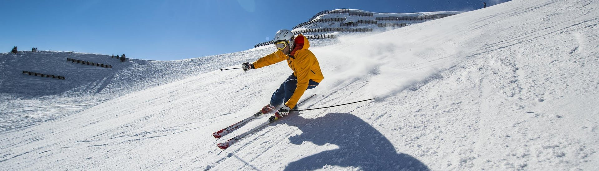Adult Ski Lessons for Beginners: A skier is skiing down a sunny ski slope while participating in an activity offered by Scuola di Sci Vigo di Fassa.