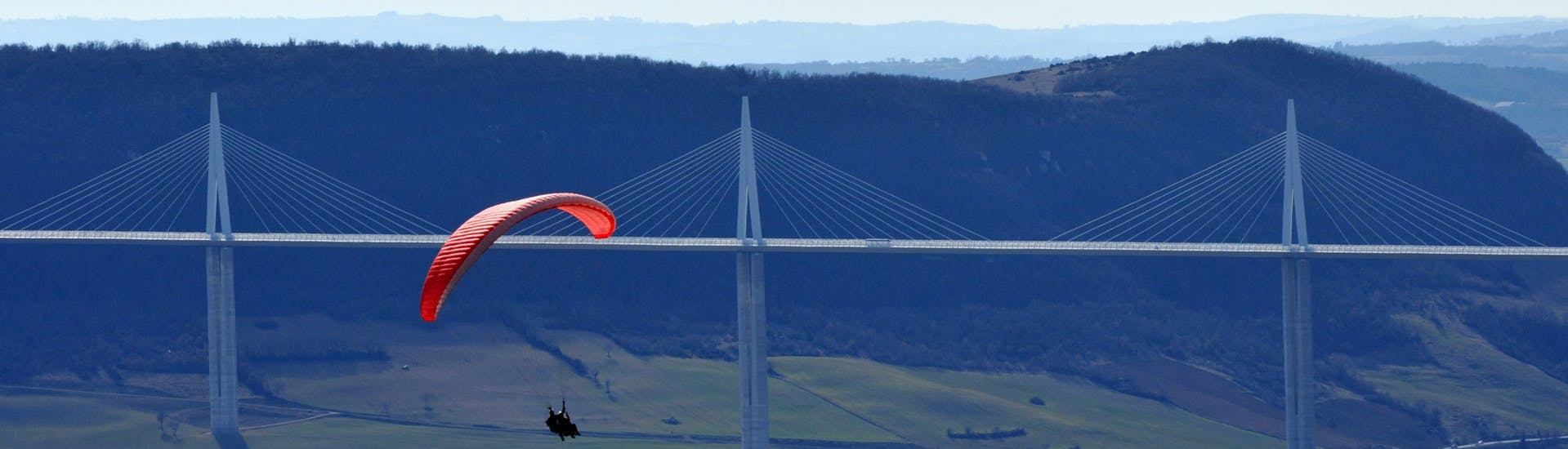 A paragliding pilot from Air Magic Parapente is doing a Tandem Paragliding Flight in front of the Millau Viaduct.