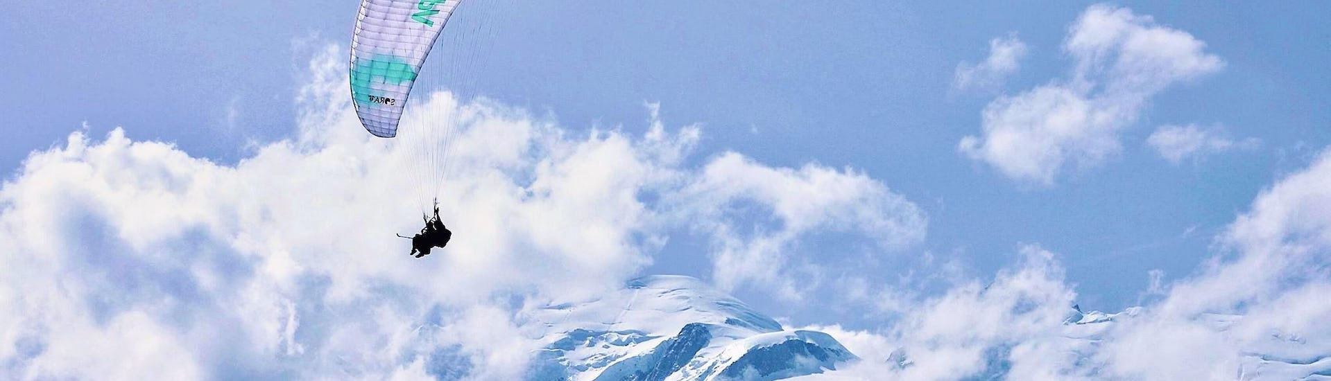 A paragliding pilot from Air Sports Chamonix is doing a paragliding flight above the Alps.