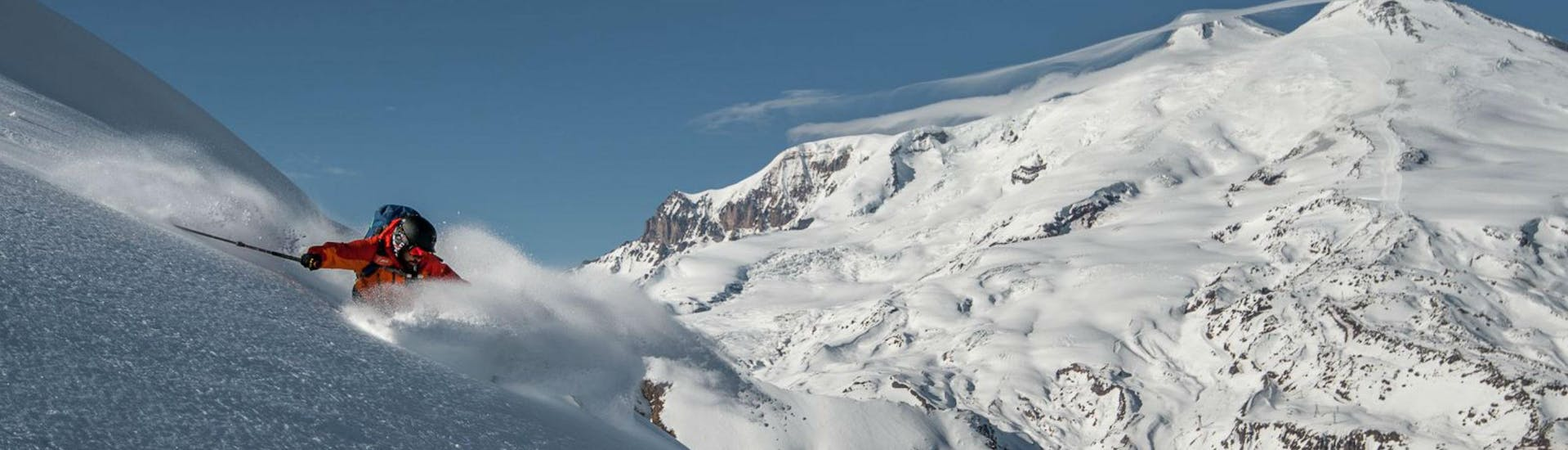 A skier is skiing through deep poweder snow while on his tour with Alpinist.