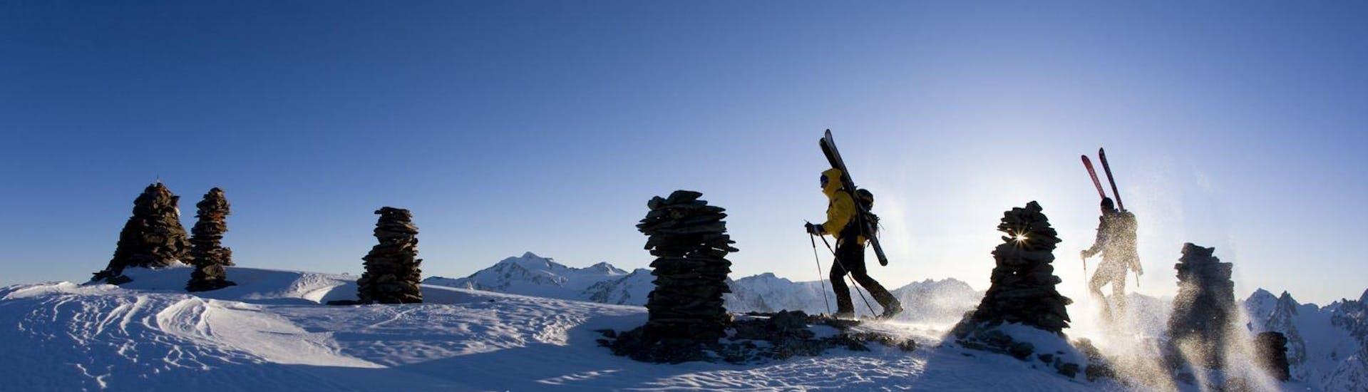 Two participants of a ski tour with Alpinschule Sölden are making their way to the mountain top in the ski resort of Sölden.