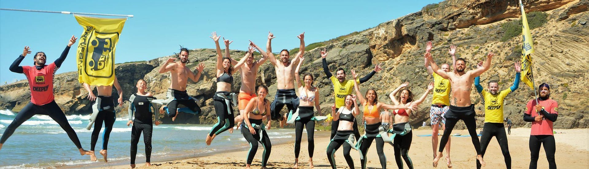 A group of happy surfers is jumping together with their surf instructors from Arrifana Surf School at the Praia da Arrifana in Arrifana.