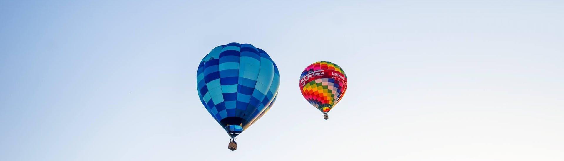Los pasajeros observan otro globo y disfrutan de la maravillosa vista con el piloto de Ibiza en Globo durante su Vuelo en globo sobre Ibiza desde San Rafael.