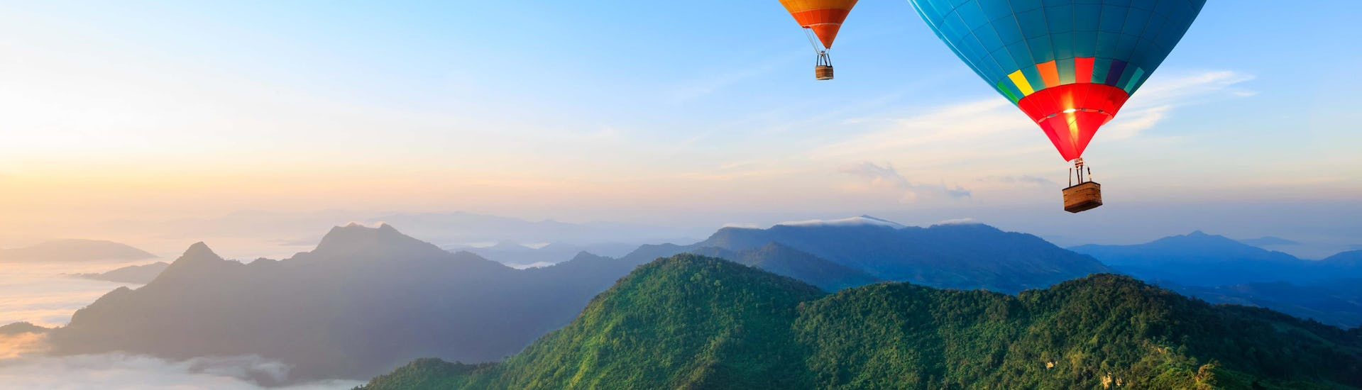 2 hot air balloons flying over a mountain landscape near the sea.