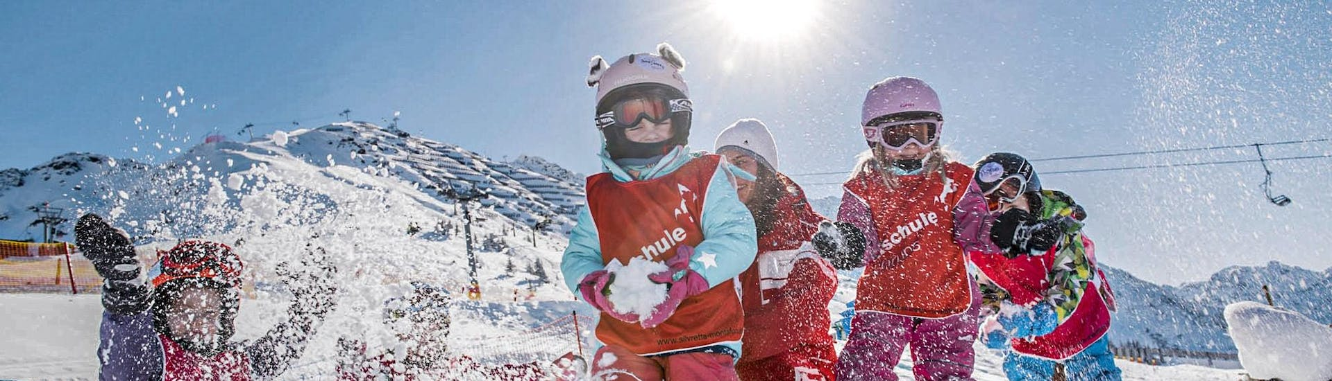 A group of young children is having fun during a snowball fight during their Bambini Kids Ski Lessons (3-5 y.) for First Timers with Skischule Schruns.v