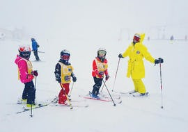 A ski instructor is with three children