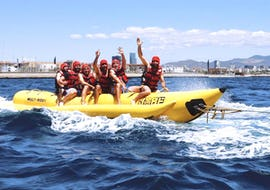 A group of friends is having fun during the Banana Boat Ride - Barcelona organised by Five Star Barcelona.