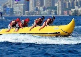 Eine Gruppe junger Menschen sitzt am Banana Boot in Benidorm und genießt bei der von Carlos Water Sports Benidorm organisierten Aktivität die aufregende Fahrt über das Meer.