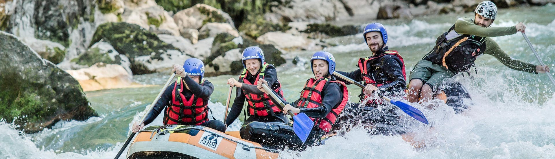 A group of friends is paddling through the rapids of the river Saalach during a rafting tour in Lofer with Base Camp.
