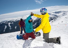 "A snowboard instructor of the snowboard school BOARD.AT helps a course participant to stand up during the snowboarding lessons ""Young Boarder Zone"" (7-14 years)."