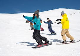 "A group of snowboarders ride down the snowy slope in slalom during the snowboarding lessons ""Basic - LTR Package"" - beginner from the snowboard school BOARD.AT"
