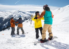 "A snowboard instructor helps the course participant to find the balance during the snowboarding lessons ""Basic"" for kids and adults of the snowboard school BOARD.AT."