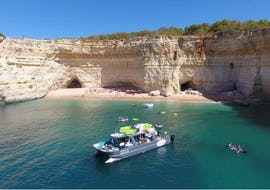 The SeaAlgarve Albufeira catamaran is anchored close to one of the many beaches along the Algarve coast during the Benagil Boat Tour with Kayak or SUP.