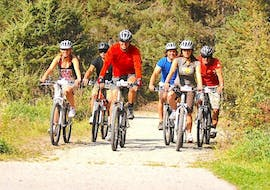 A group of cyclists is cycling along a pathway in the woods during their Mountain Bike Tour to Lake Ambergersee with CanKick Ötztal.