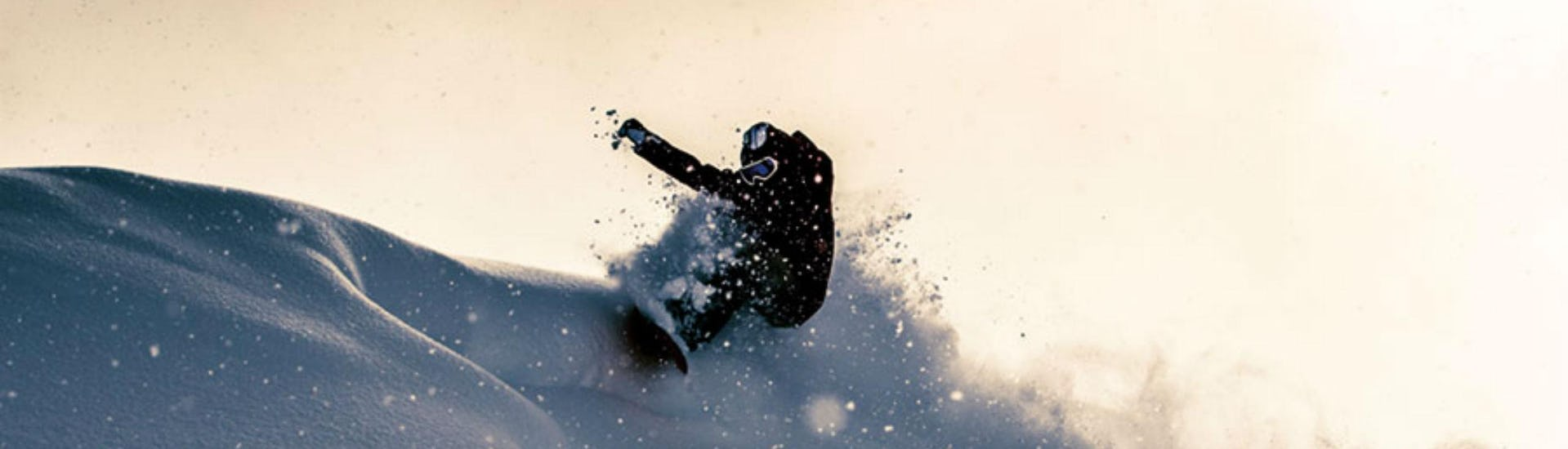 A snowboard instructor from Board.at is doing some freestyle tricks in the powder snow.