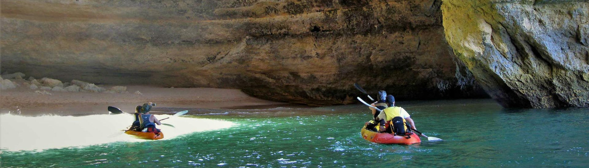 A group of kayakers is paddling into the Benagil Cave during their Boat and Kayak Tour - Benagil Cave with Seasiren Tours.