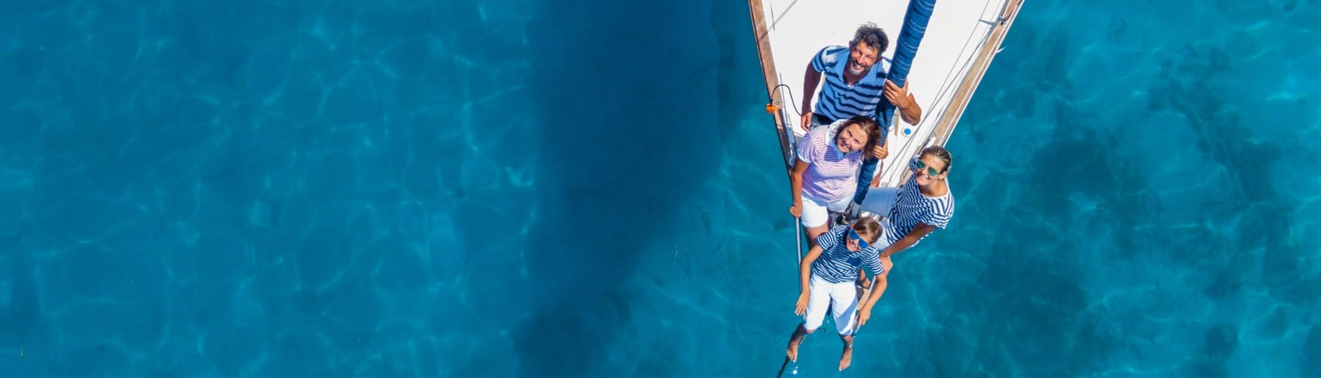 A family is sailing across clear blue waters on a vessel chartered from a boat rental.