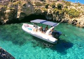Un bateau semi-rigide mouille dans une crique tranquille pour une baignade dans l'eau cristalline pendant la Sortie privée en bateau autour des grottes de Gozo avec Vitamin Sea Gozo.