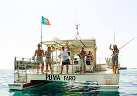 The passengers of the Boat Tour to the Rocks and Caves of Benagil from Vilamoura organized by Cruzeiros da Oura Vilamoura are waving at the camera as they are heading to sea.