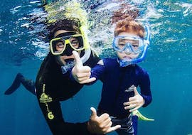 A father is enjoying a guided snorkeling with his son during the Boat Tour with Snorkeling on the Great Barrier Reef organised by Passions of Paradise.
