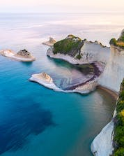 An image of Cape Drastis with its white cliffs, a popular sight during many boat tours on Corfu.