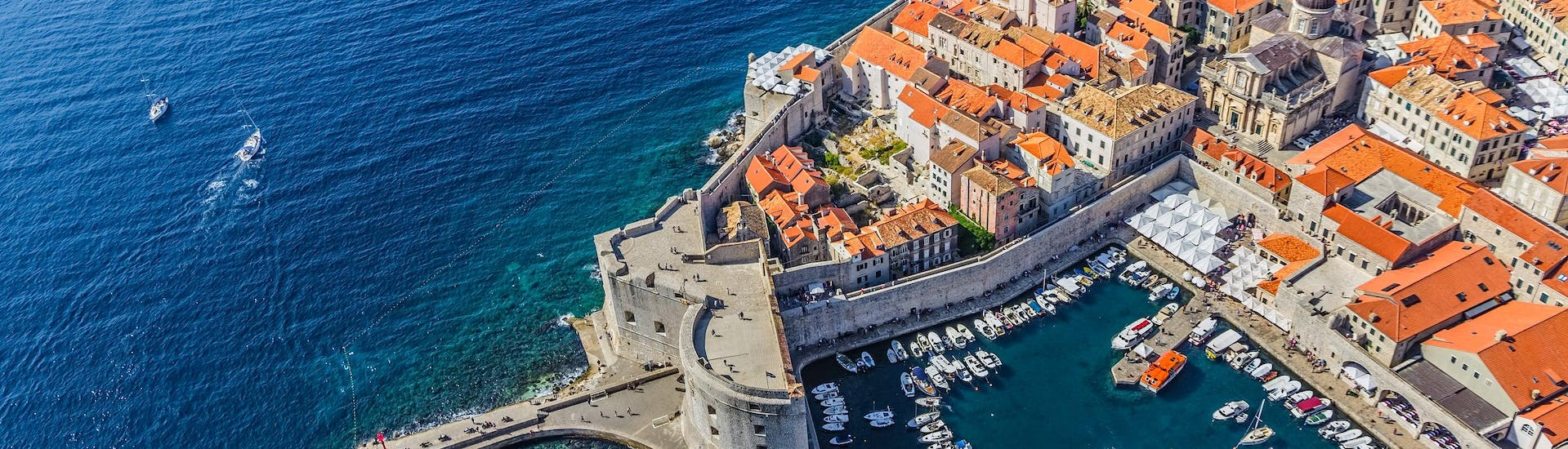 An aerial view of several boats anchored in the old port, a common departure point for boat tours in Dubrovnik.