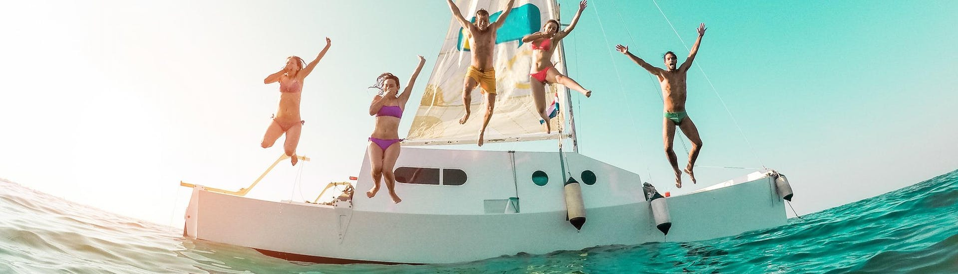 A group of friends is jumping into the sea during their boat trip in Ibiza.