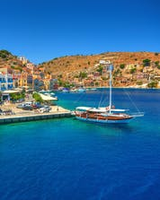 An image of a small harbour where a sailing boat is about to depart on a boat tour around Rhodes.