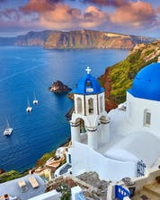 A stunning scene of the sun setting over Oia, a spectacle that can be witnessed on a boat tour in Santorini.