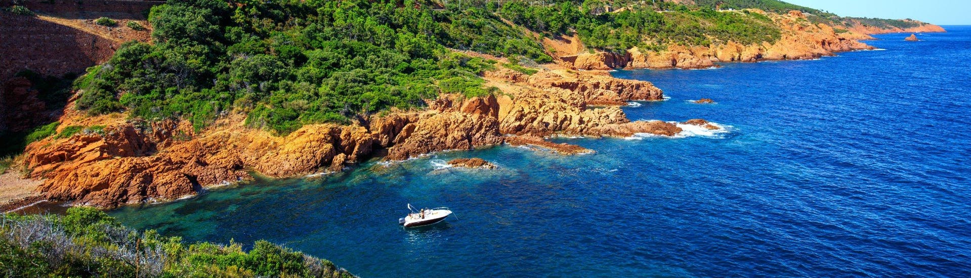 A boat is cruising along the coastline of the L'Estérel Natural Park, which is a popular destination for boat trips from Cannes.